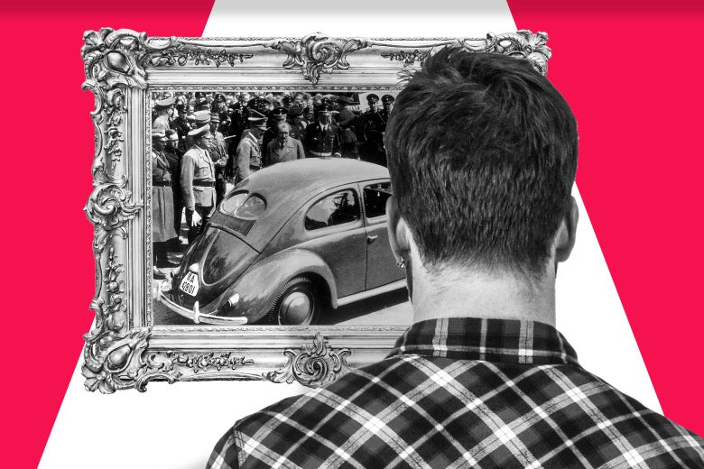 A man seen from the back looking at a framed image of Hitler in a crowd of people looking at a Volkswagen car.