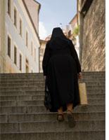 Nun climbing stairs in Prague