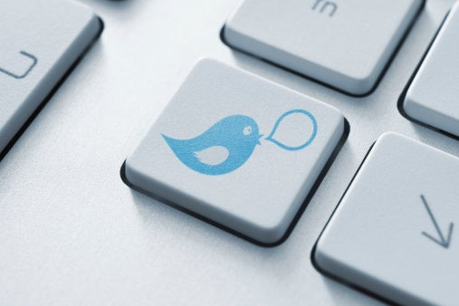 A close-up of a keyboard, one key of which has the blue Twitter bird logo on it.