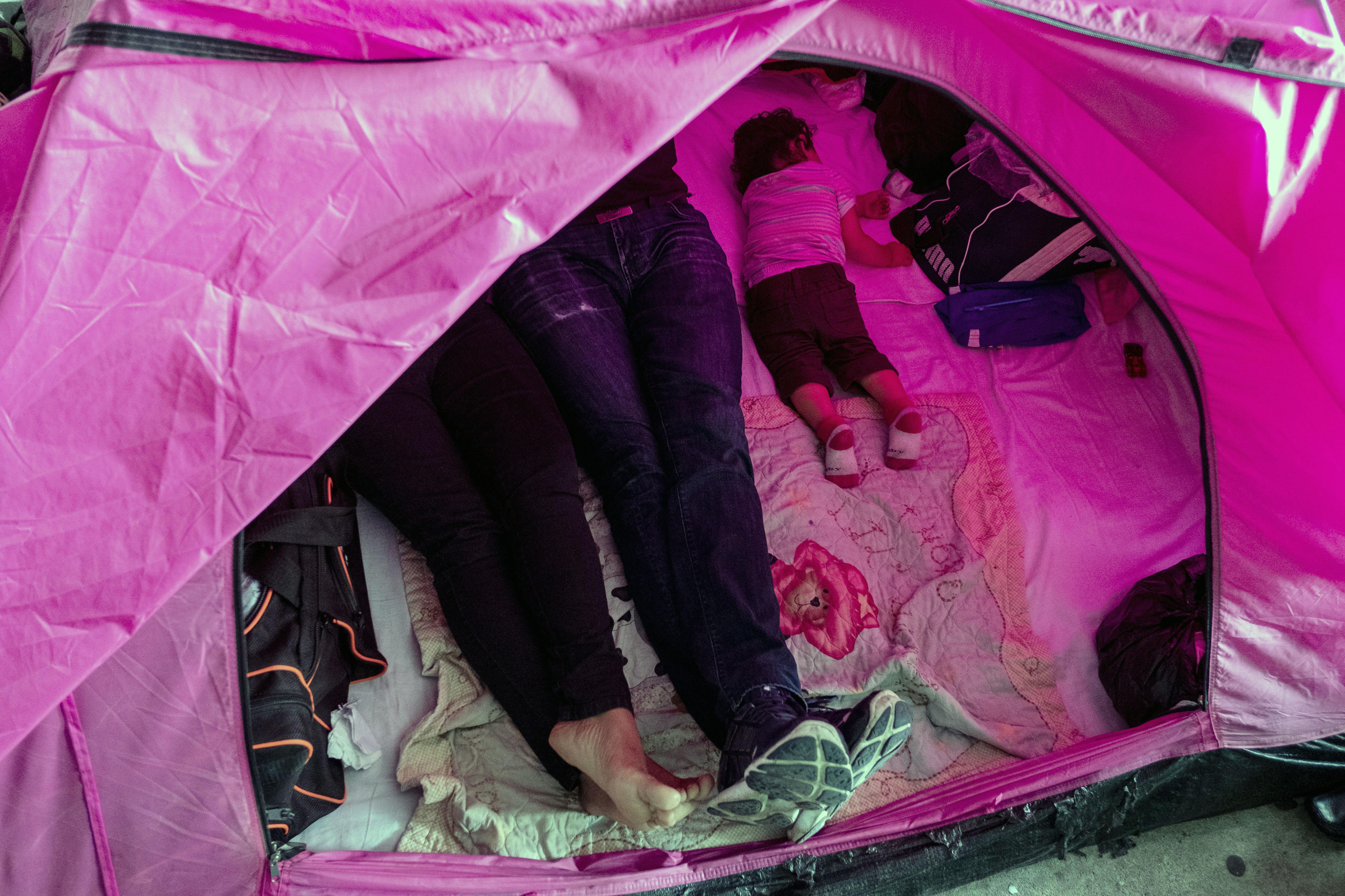 Asylum seekers from El Salvador rest in their tent in the Juventud 2000 migrant shelter in Tijuana on Wednesday.