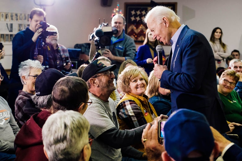 Biden, standing, shakes the hand of a man seated in the audience of a town hall–style event.