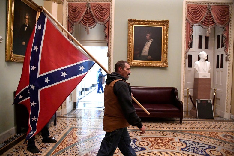 A man carries a Confederate flag over his shoulder.