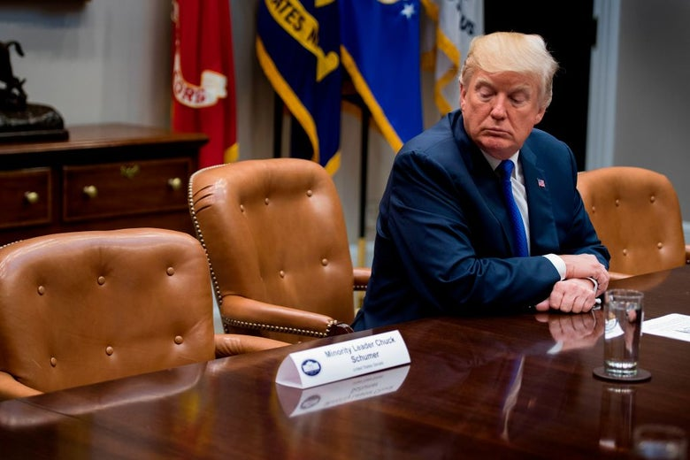 Trump sits at a long and otherwise empty table.