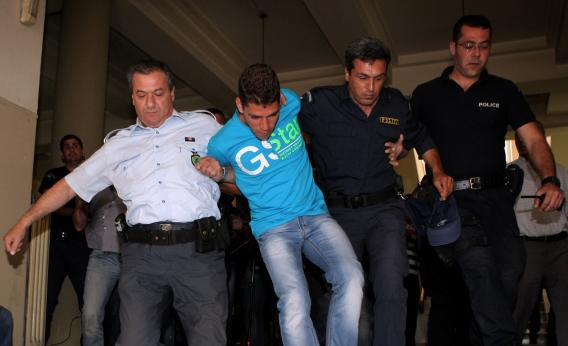 Police officers drag to prosecutor a 20-year-old Dutch entertainer in Herakleion, Crete, on May 16, 2013.
