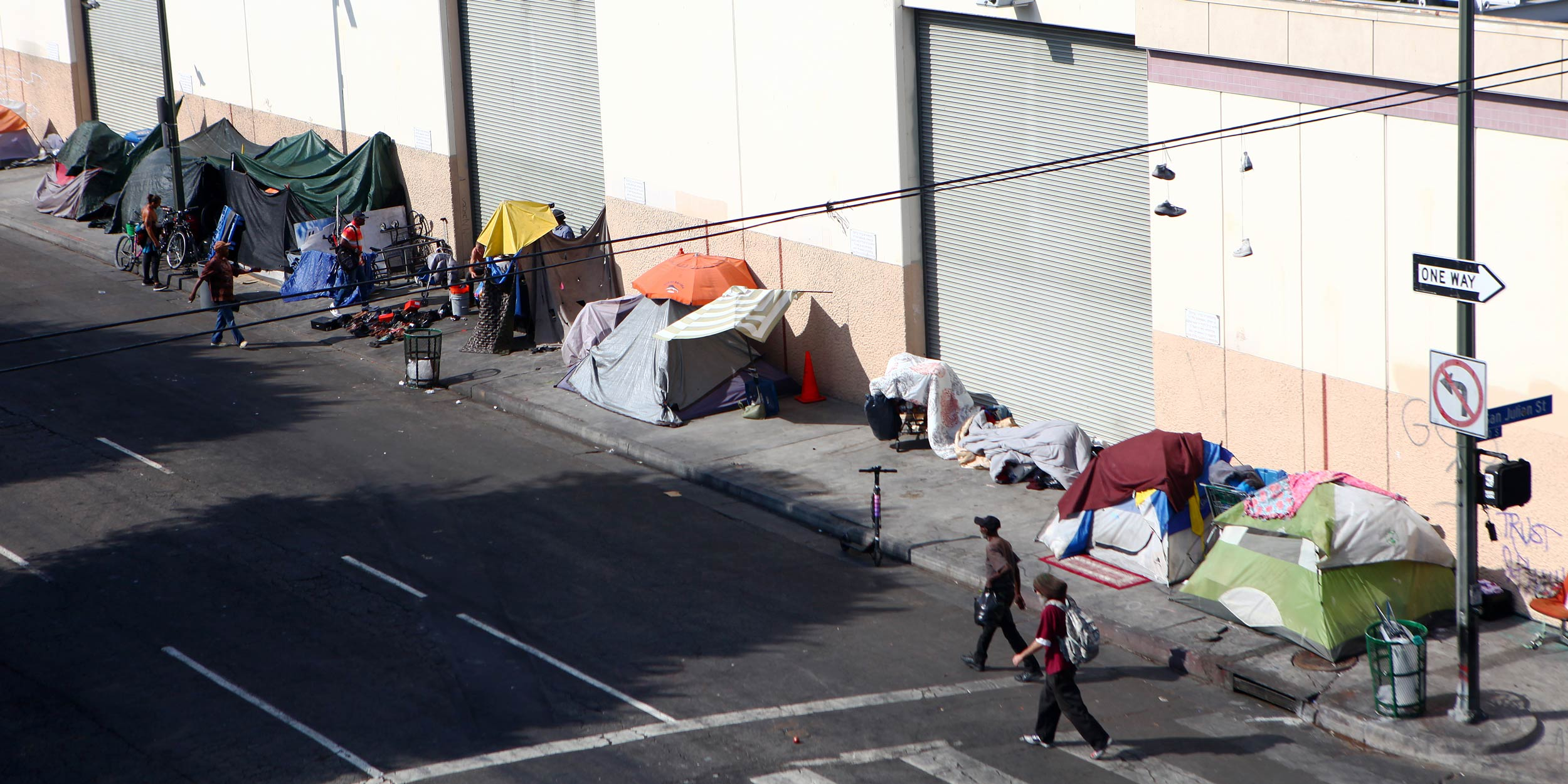 People walk past a homeless tent encampment in Skid Row.