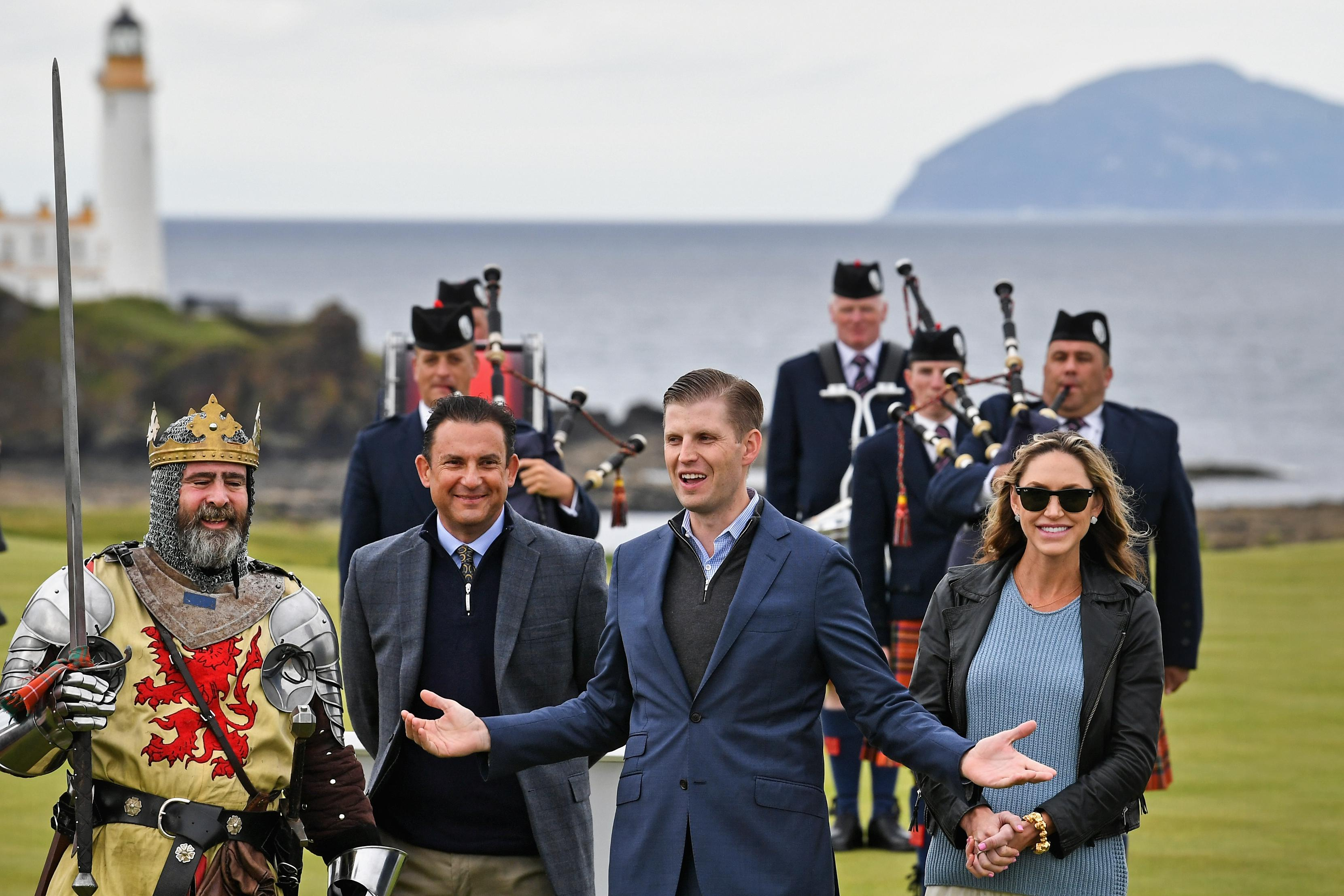 Eric Trump and his wife, Lara, at Turnberry golf course, surrounded by a man dressed as a knight and other men in kilts.