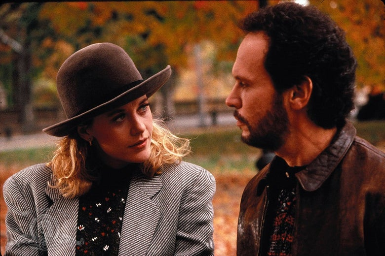 Meg Ryan, wearing a large brown hat and a gray blazer, looks at Billy Crystal in profile.