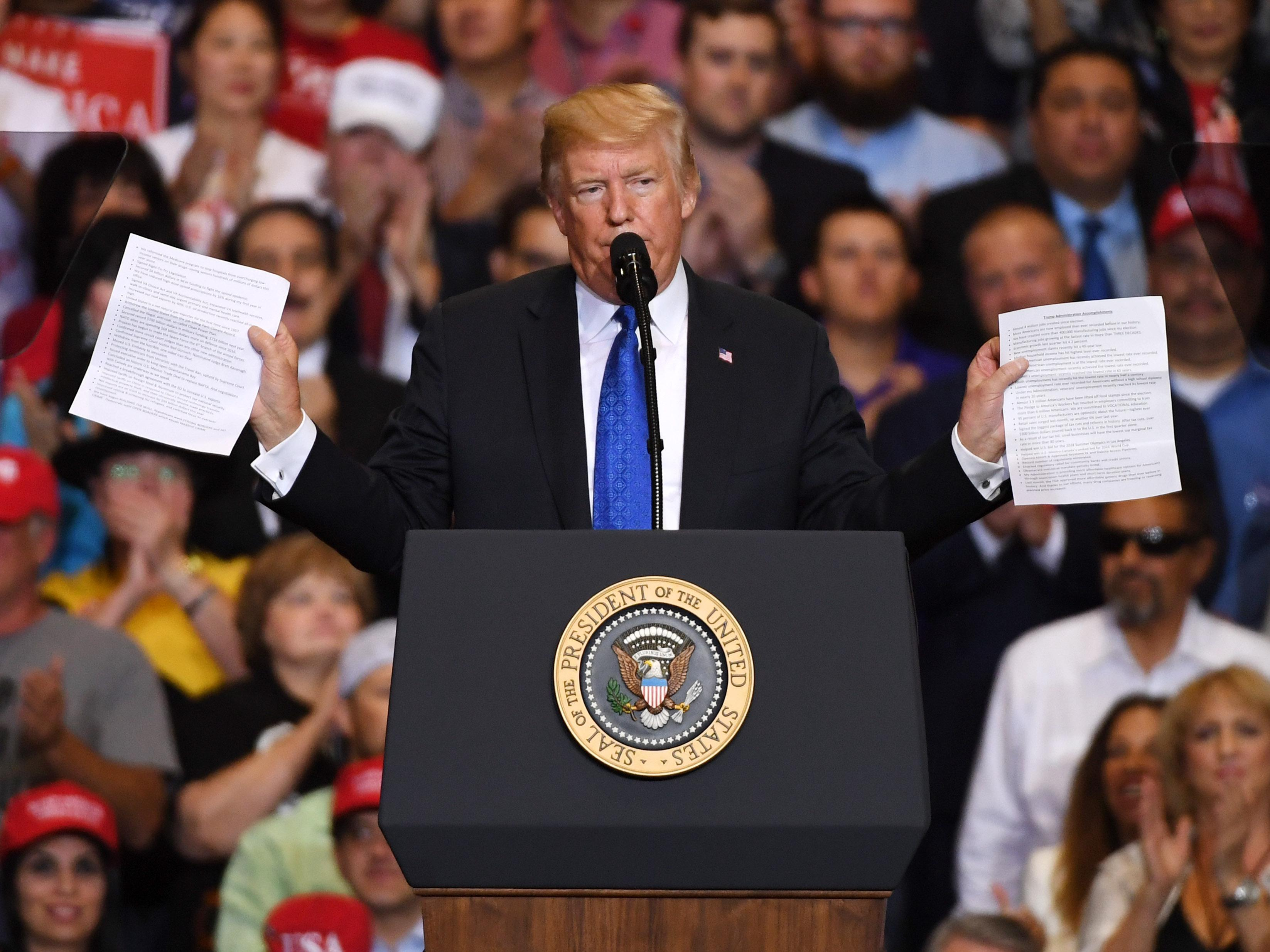 President Donald Trump holds up two sheets of paper while speaking behind the podium during a campaign rally at the Las Vegas Convention Center on Sept. 20, 2018.
