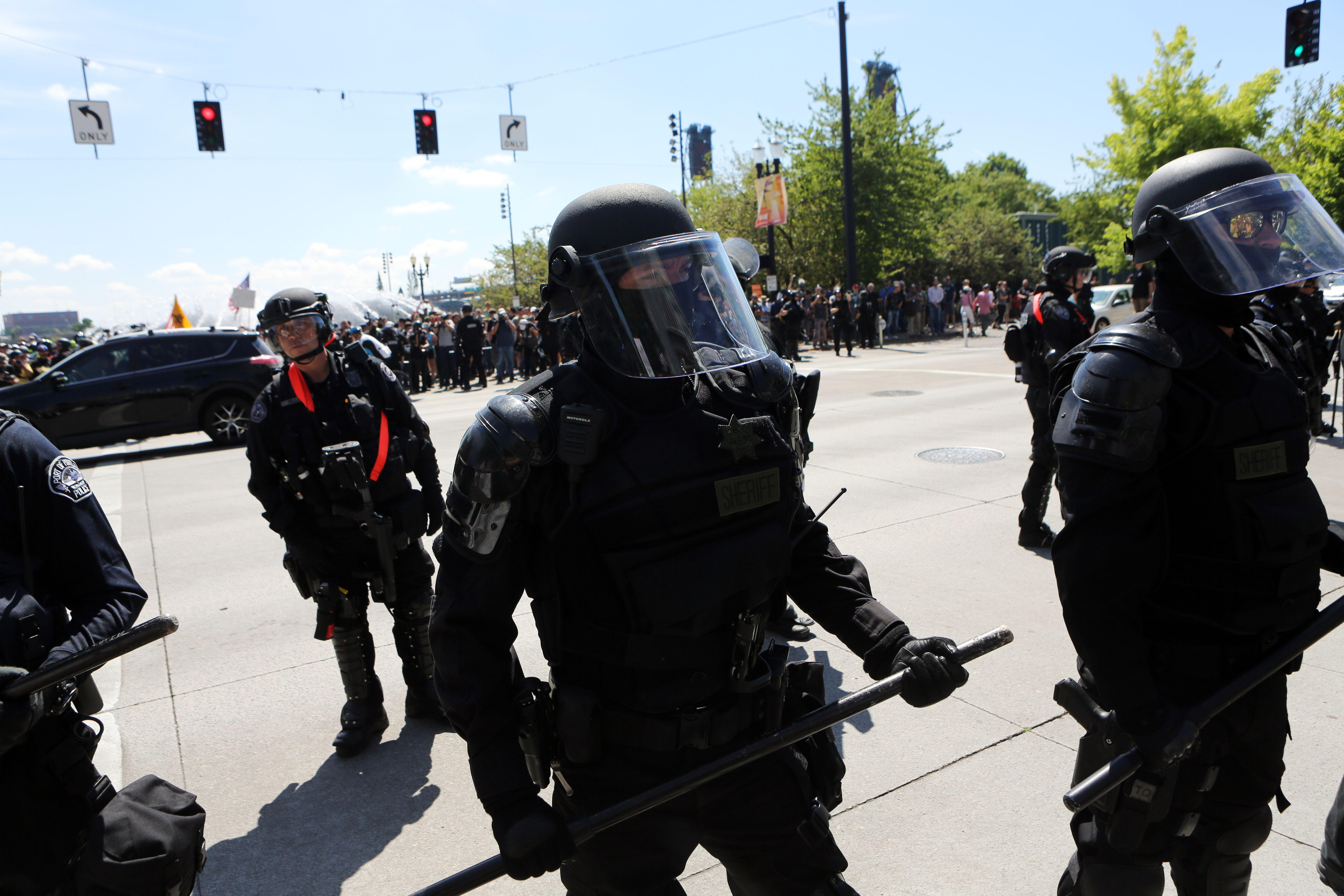 Police in riot gear stand at an intersection.  On the other side of the intersection, crowds of protesters can be seen.