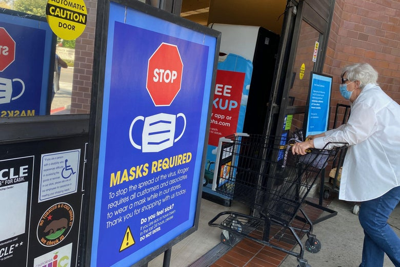 """A shopper with a cart enters a store where it says, """"Mask required"""" outside the doors."""