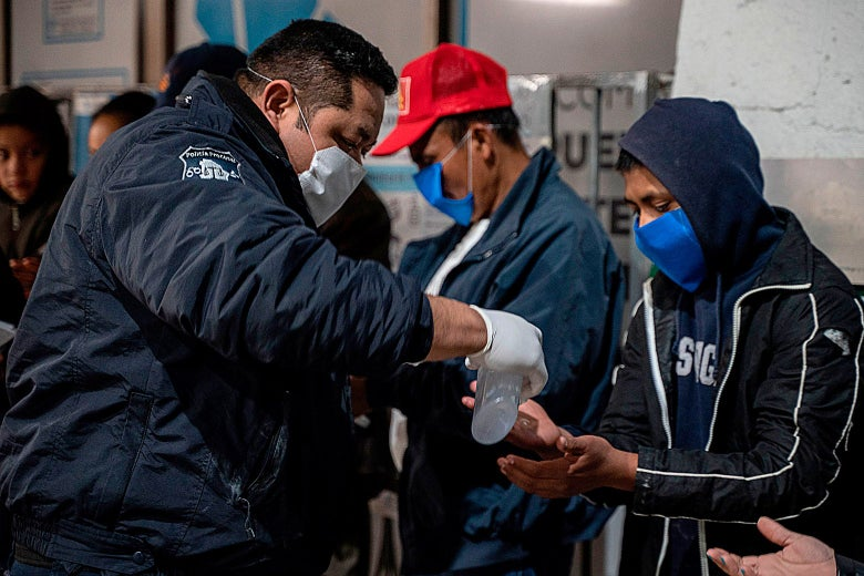 Chihuahua State Police give out hand sanitizer to migrants on April 6 at the Paso del Norte International Bridge in Ciudad Juárez in Chihuahua, Mexico.