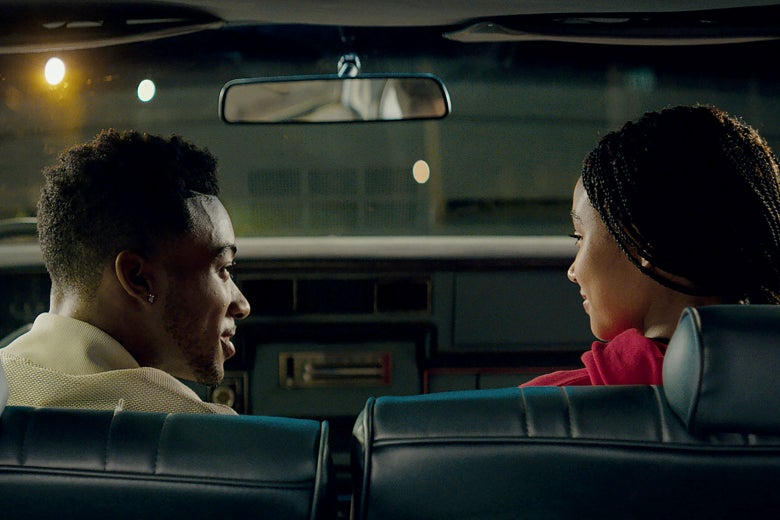 In a scene from The Hate U Give, a young black man and a young black woman look at each other admiringly in the front seats of a car.