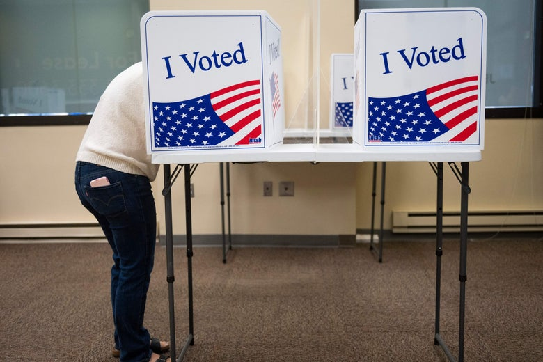 A man with his head in a voting booth.