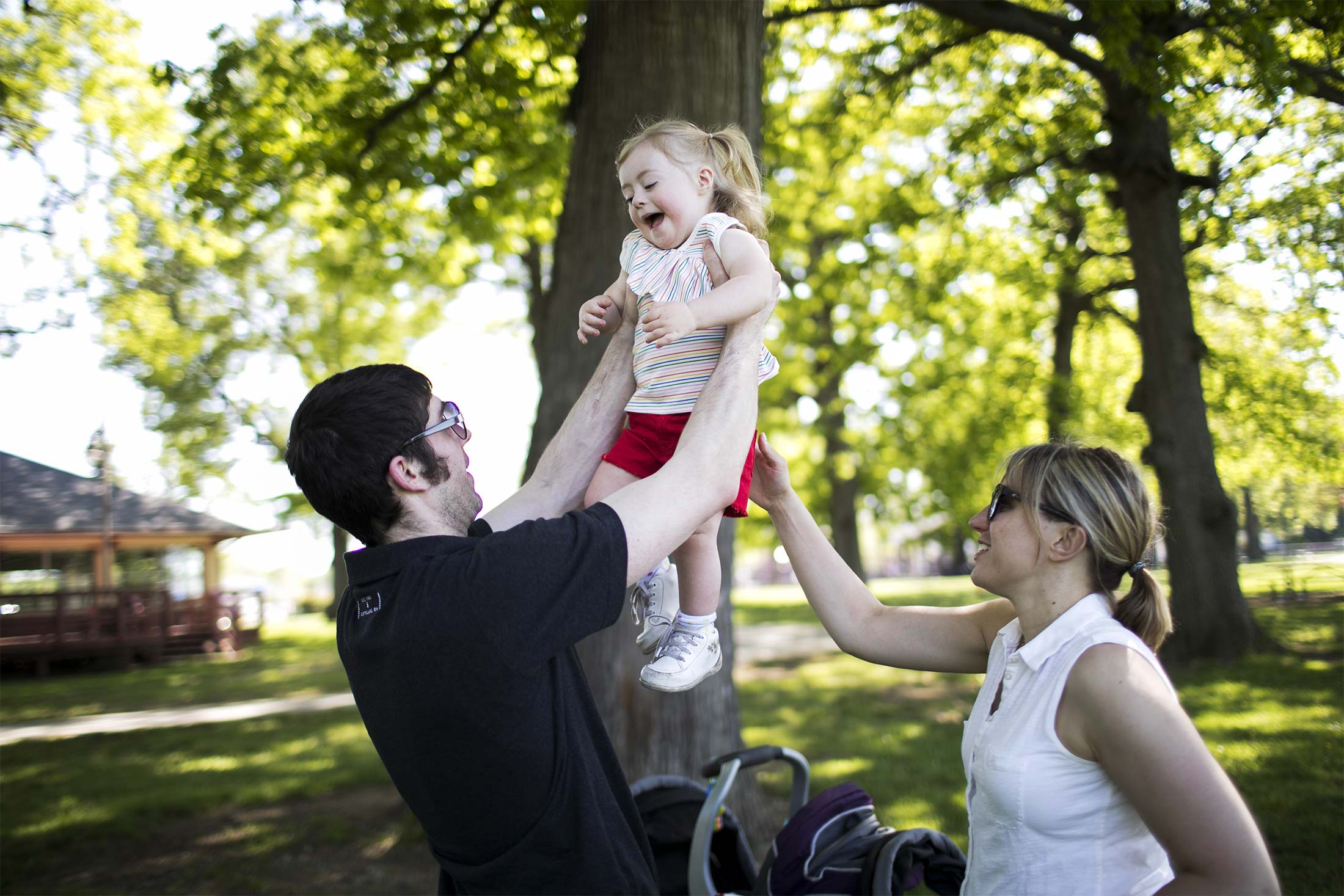 Patrick lifts his daughter, Clementine, at a park as Celeste watches.