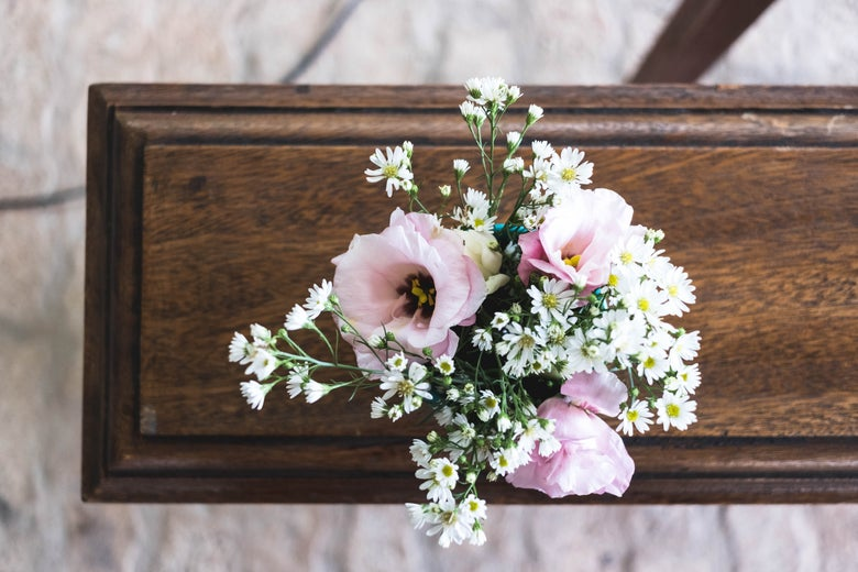Flowers sit on top of a wooden casket.