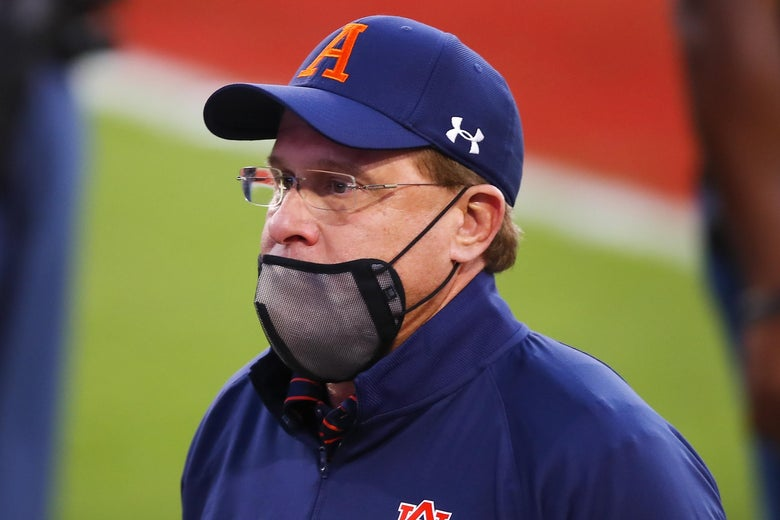 Gus Malzahn in an Auburn hat with a mask pulled under his nose, on his chin