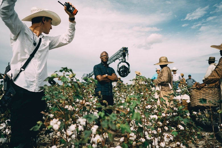 Barry Jenkins stands in a field with his arms crossed with crew and cast around him.