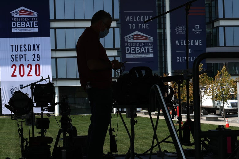 A man works on TV cameras on a stage with debate signs.