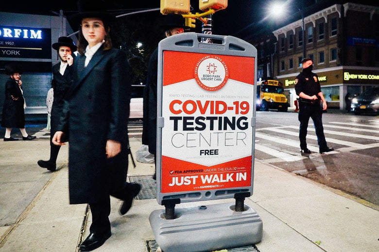 A boy in traditional Hasidic dress walks by a sign that says COVID-19 Testing Center.