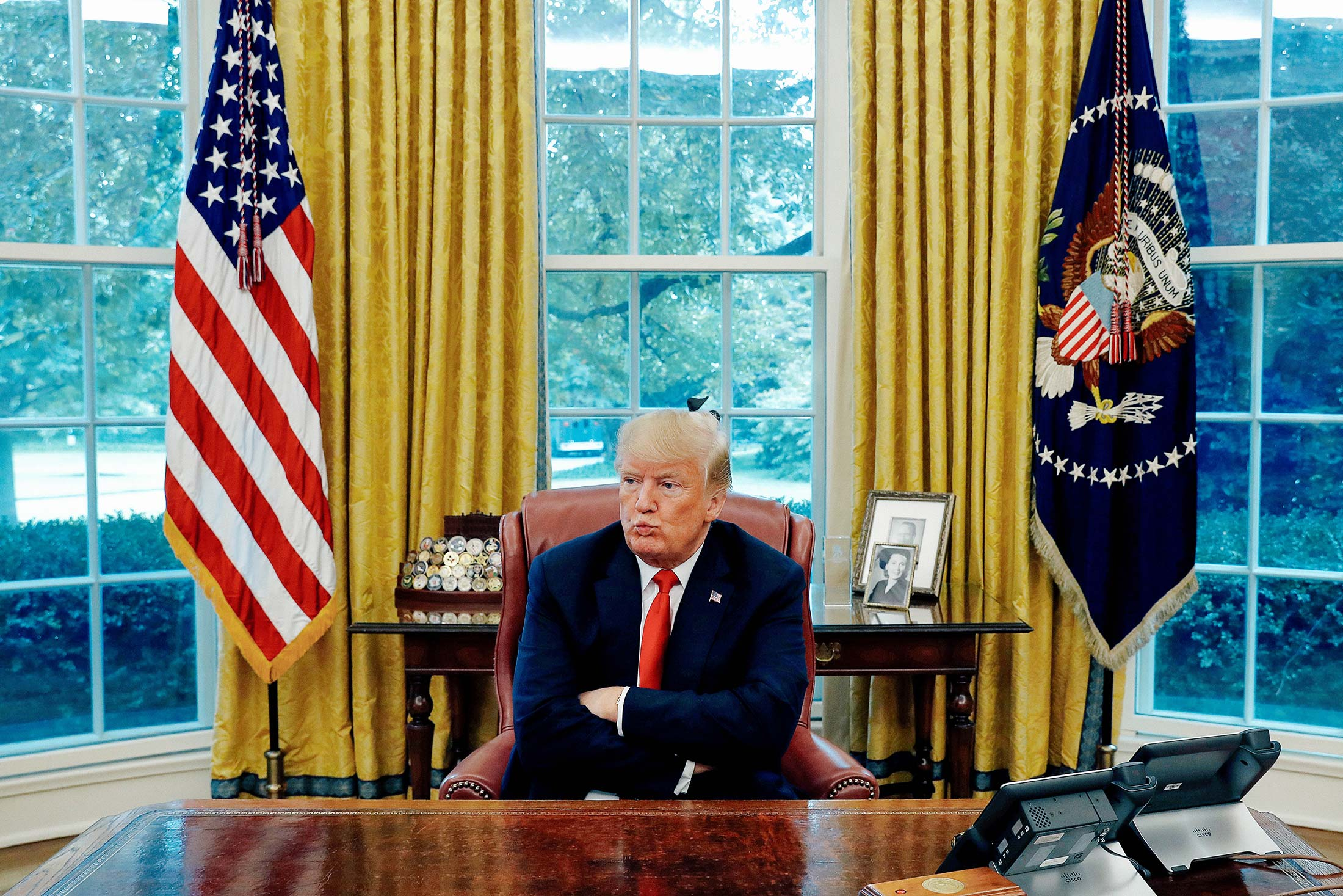 Donald Trump crosses his arms across his chest while sitting behind his desk in the Oval Office.