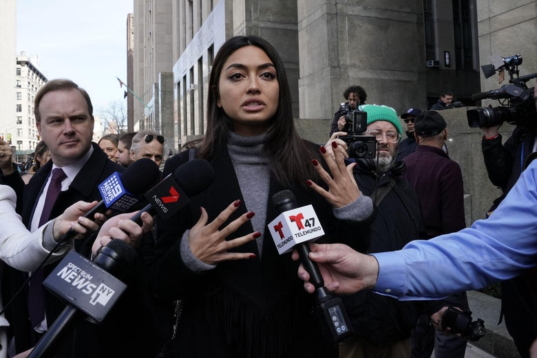 A woman in a black jacket and turtleneck stands outside a courthouse talking to reporters, surrounded by microphones.