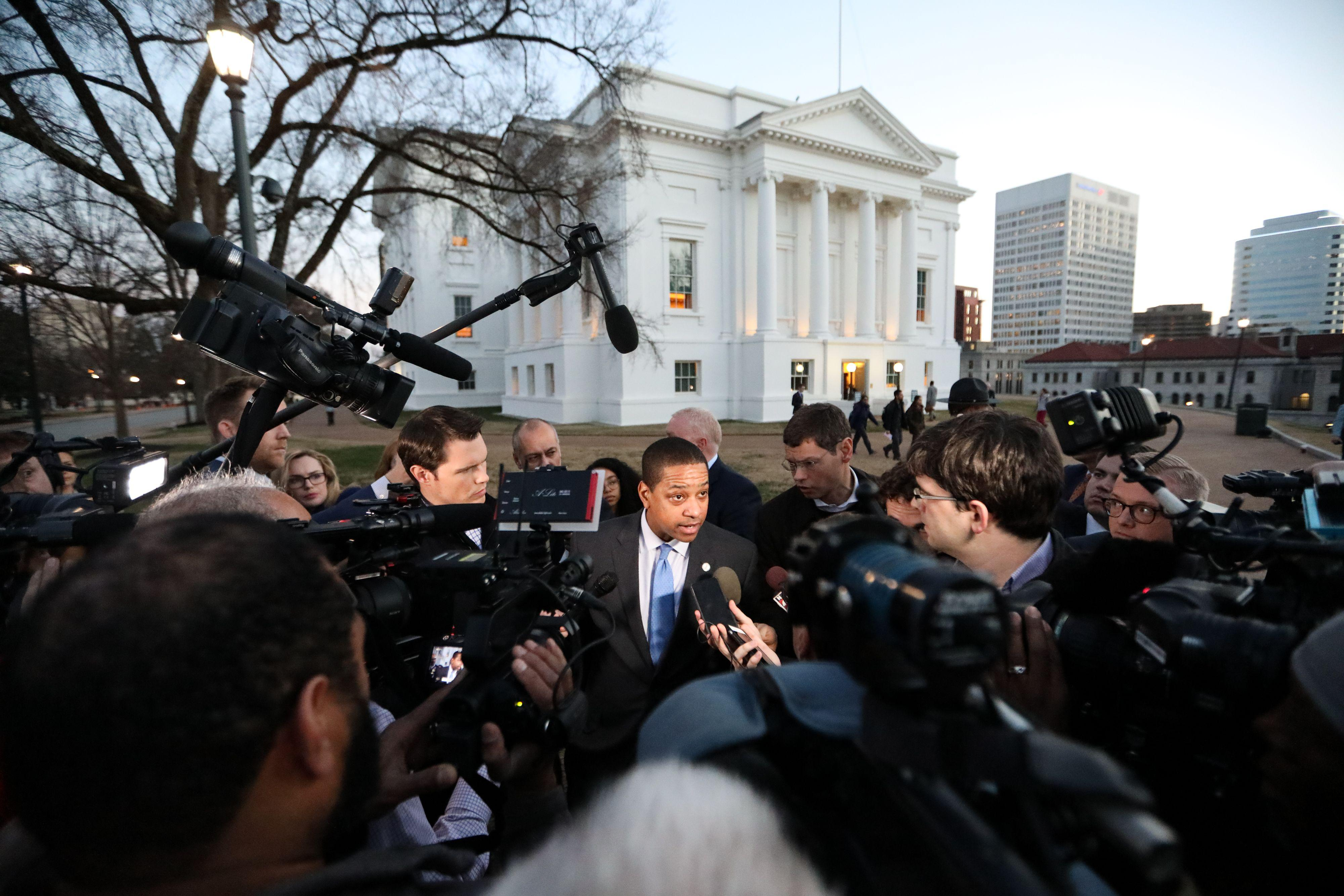 Virginia Lieutenant Governor Justin Fairfax stands in the middle of a scrum of reporters with cameras and mics outside the Virginia capital building.