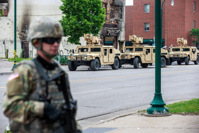 Armored vehicles roll down the streets of Minneapolis. A uniformed guardsman stands in the foreground.