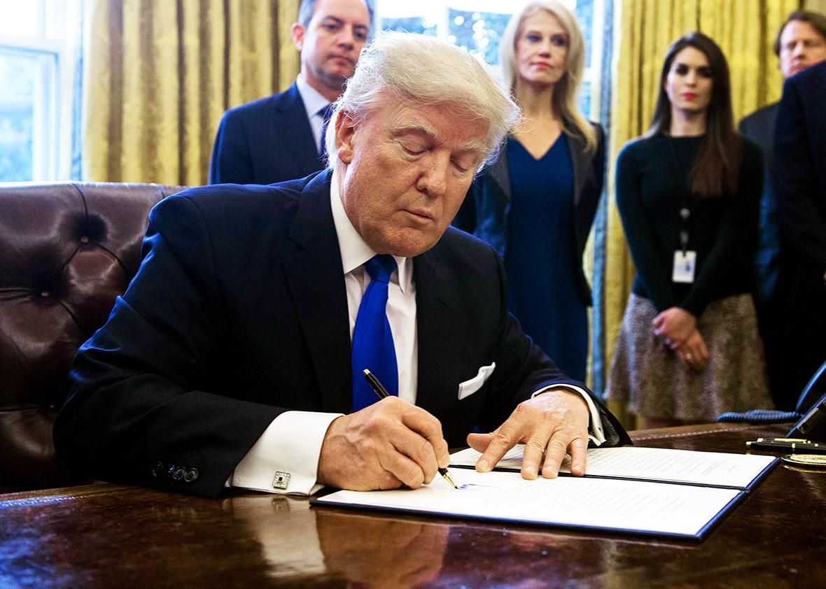 US President Donald Trump signs an executive order in the Oval Offoice at the White House in Washington, DC, on January 24, 2017.