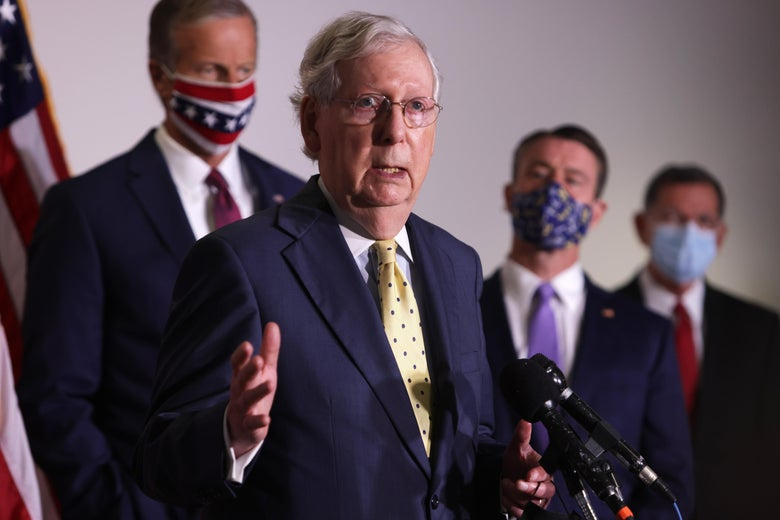 Mitch McConnell speaks to the media, with masked staffers standing behind him