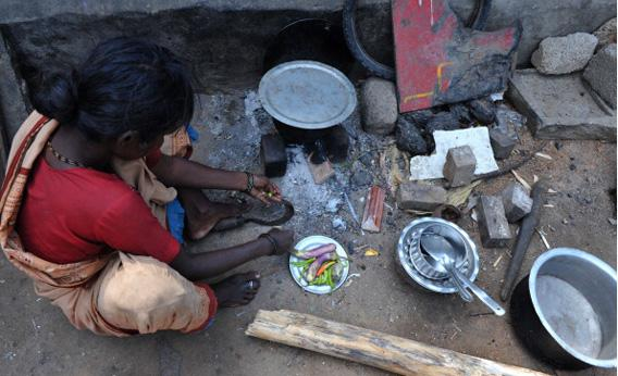 An Indian woman cuts vegetables to cook on the roadside at a temporary shelter