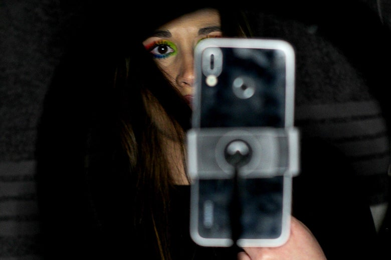 A person partially visible behind a smartphone on a stand.