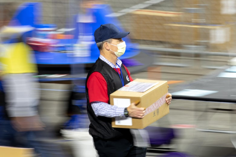 A man in a surgical mask carries a cardboard box.