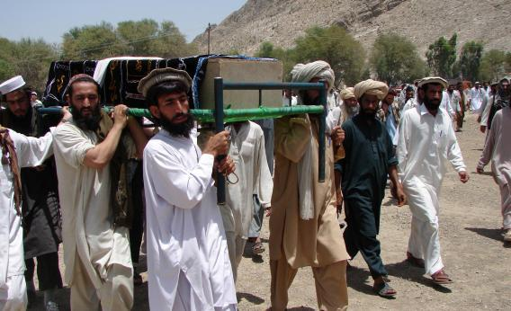 Pakistani tribesmen carry the coffin of a person allegedly killed in a 2011 U.S. drone attack. They claim that innocent civilians died.