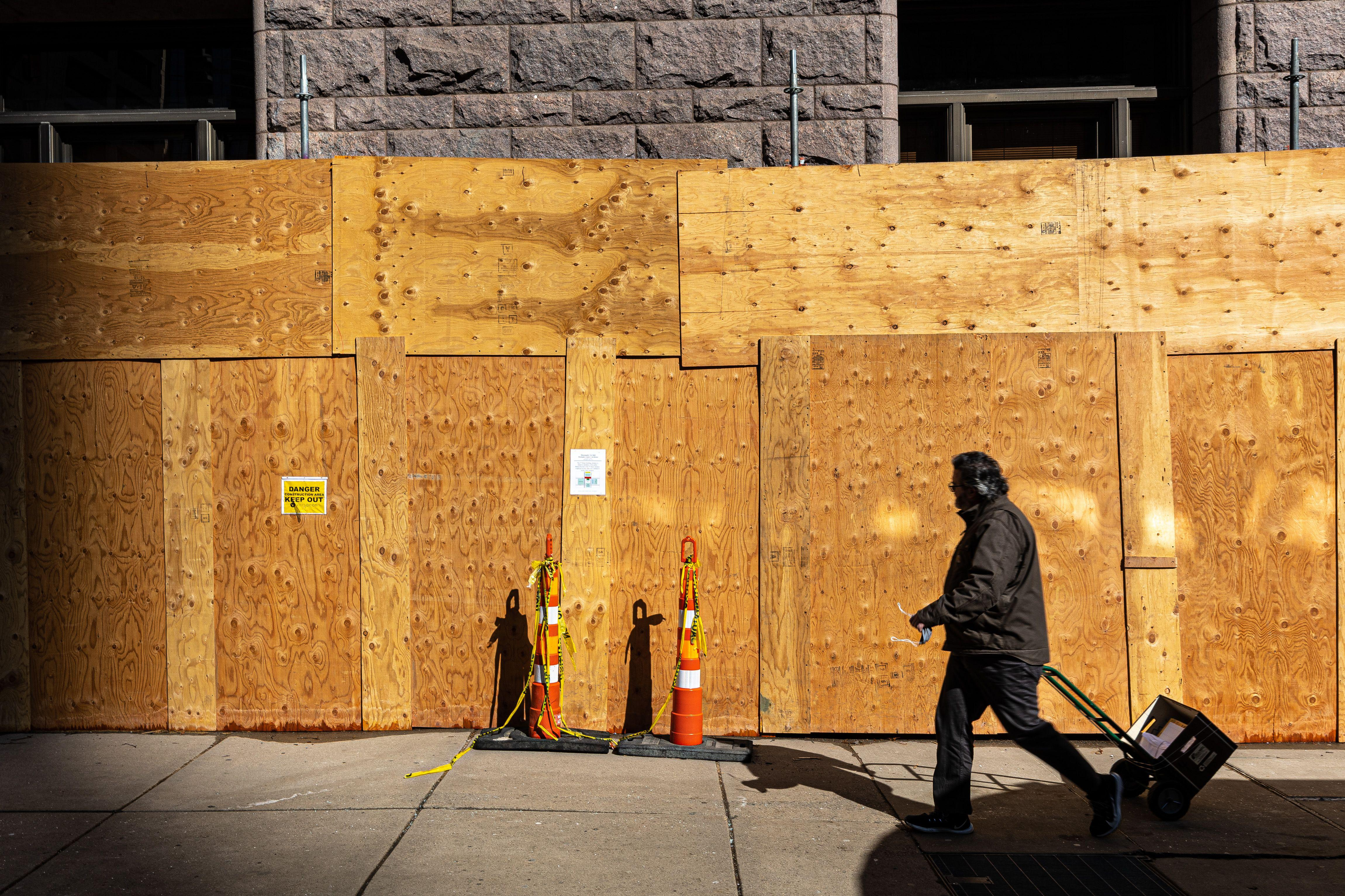 A man walks with court files past boarded windows at the- Hennepin County Government Headquarters in Minneapolis, Minnesota, on March 3, 2021.