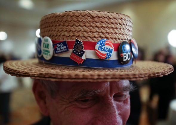 Hank Schwab shows off the campaign hat he's worn for the past 30 years at a gathering in support of Republican U.S. Senate candidate David Perdue on Nov. 4, 2014, in Atlanta