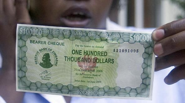 A Zimbabwean Woman Displays The New 100 000 Dollar Bill