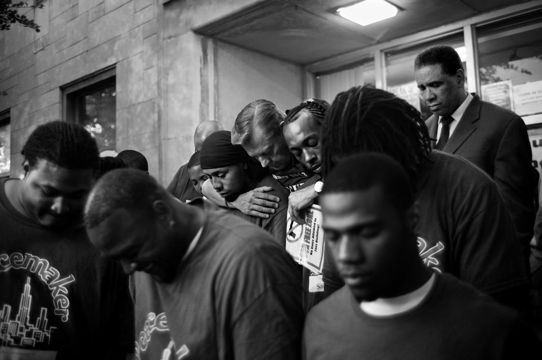 PG 128-129: Father Mike of St. Sabina Church hugs young men who work to break the cycle of violence during a prayer service. Auburn Gresham, Chicago, 2013