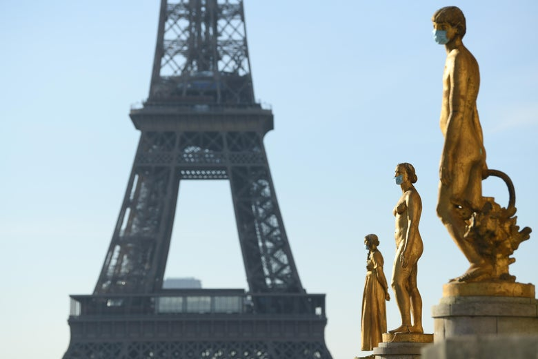 The middle of the Eiffel Tower is seen in the background. One the right, three golden statues of women wear surgical face masks.