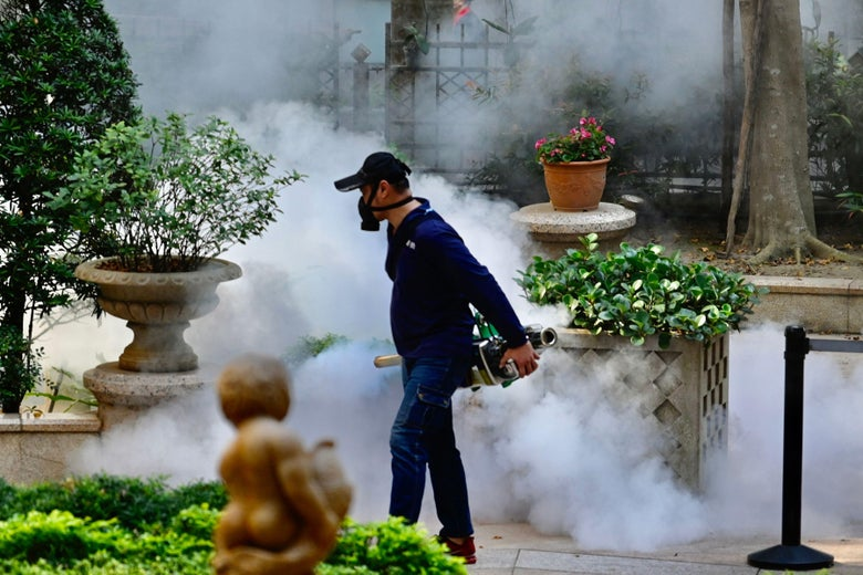 A mask-clad worker with a handheld machine walks on a street amid potted plants before billows of smoke.