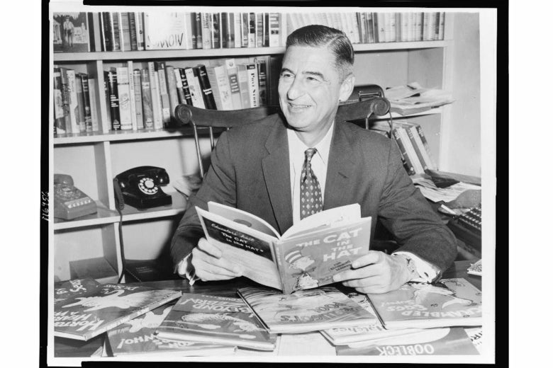 A black-and-white photo of Dr. Seuss sitting at his desk with his books