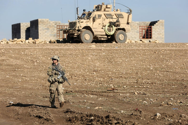 U.S. soldier on patrol with armored vehicle in stark landscape in front of small down near Mosul