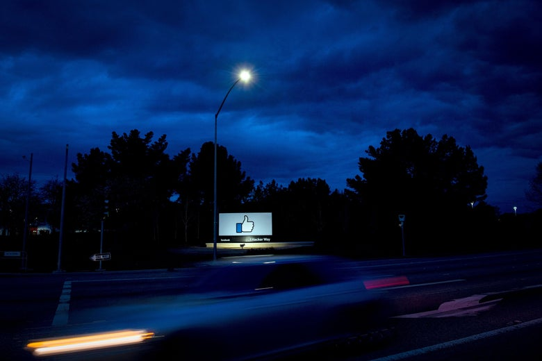 A Facebook billboard featuring the like button, by the side of a highway at night.