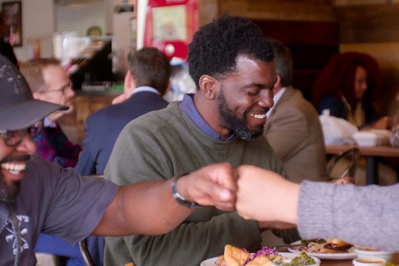 One Black man smiles as another Black man fist bumps across a table laden with food