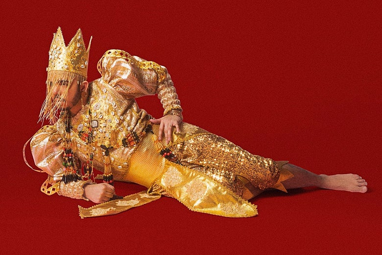 Crown album cover featuring Aja in a gold outfit, crown, and veil lying on their side on a red background