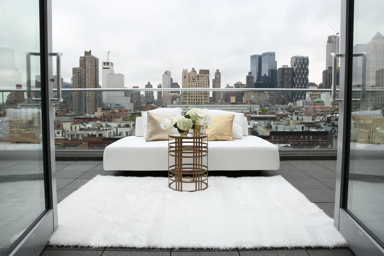 A white couch sits on a balcony overlooking New York City.