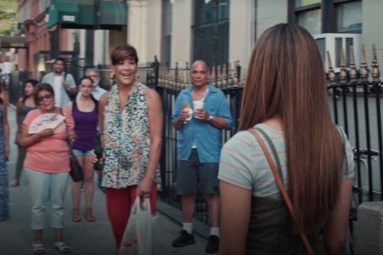 Doreen Montalvo stands amidst a crowd of people on a sidewalk. In the foreground, Nina stands with her back turned to the camera.