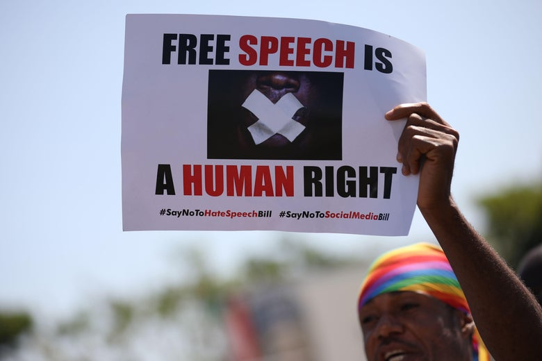 """A protester holds a placard that reads """"Free Speech Is a Human Right."""""""