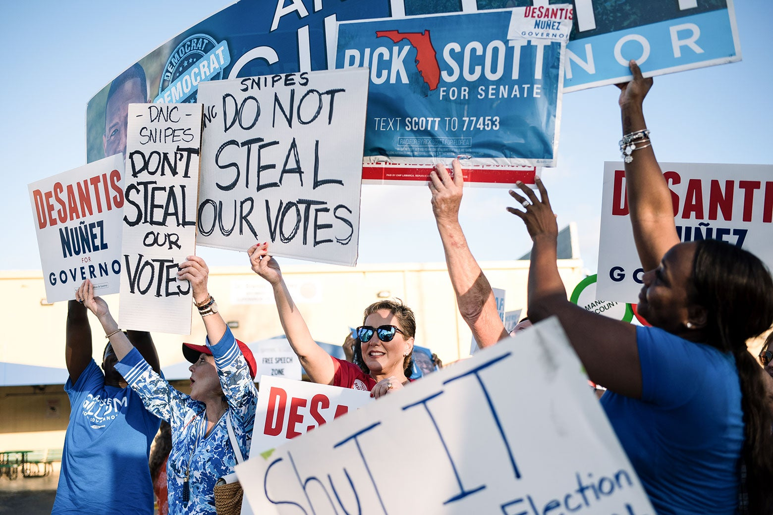 Various protesters hold up signs in support of Ron DeSantis, Rick Scott, and Andrew Gillum.