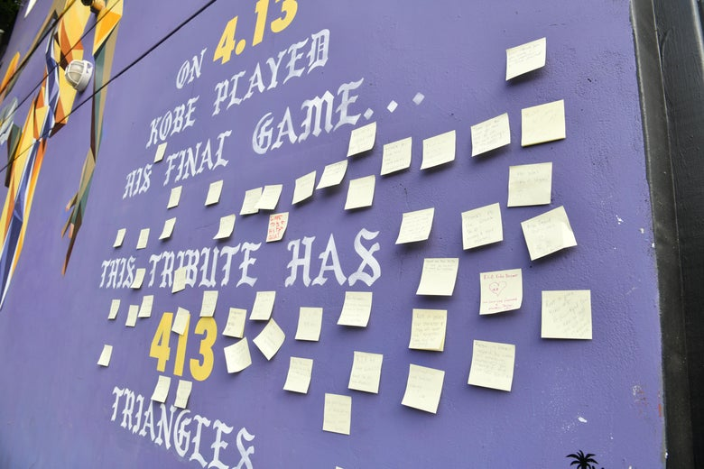 A Los Angeles wall mural depicting Kobe in his Lakers uniform, covered with post-its with notes from mourners.