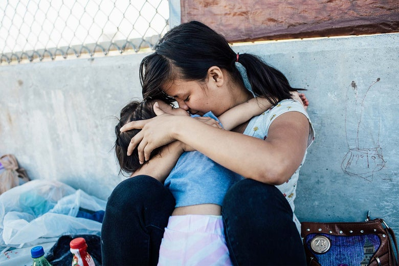 A Honduran woman embraces her 2-year-old daughter as they wait on the Mexican side of the Brownsville & Matamoros International Bridge.